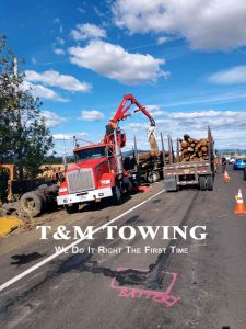 Tow Company placing logs onto backup trailer